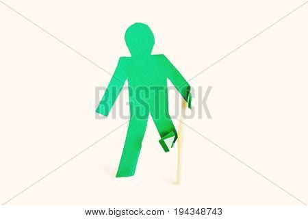 An injured green stick figure with a walking stick over white background