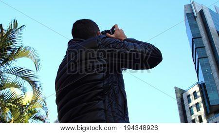 Young man photographing Paulista Avenue - Sao Paulo city, Brazil