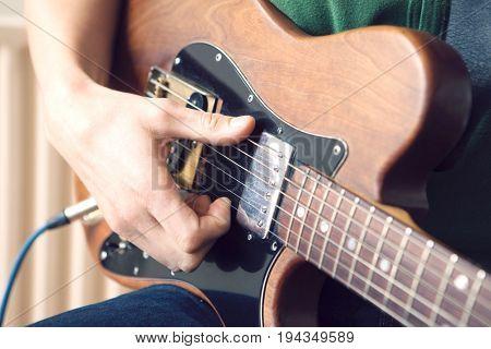 Man Strums Chord On Guitar