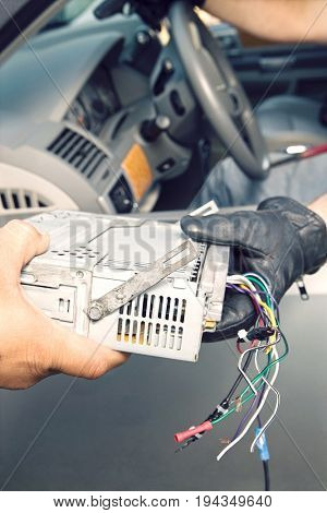 Hand in leather glove handing over a stolen car radio to man