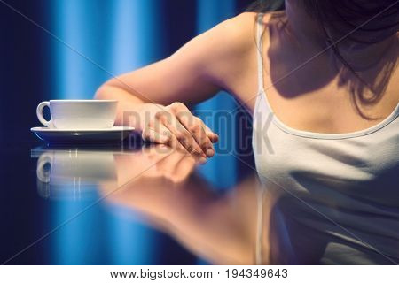 Closeup midsection of a young woman with teacup in cafe
