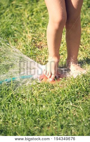 Lowsection of a little girl playing with lawn sprinkler