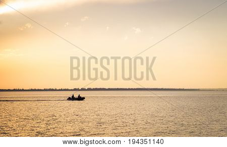 Fishermen sail on a motor boat on the evening estuary before sunset is very bright and beautiful
