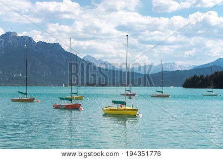 Small colorful sailboats anchoring in turquois alpine lake in front of mountains. Bavaria, Germany, Allgau, Forggensee.