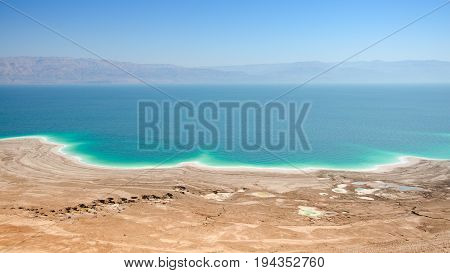 Aerial panoramic landscape of Dead Sea lake with salt water and curative mud shores beaches