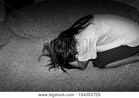 Sad lonely young woman sitting alone and depressed on the bed in her room and pulling her hair. Black and white. Dark image.