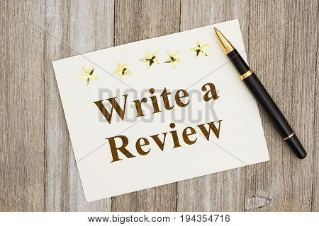 Write a Review text on a greeting card and a pen and five good stars on weathered wood