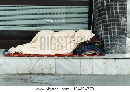 Poor homeless person, covered with a blanket, sleep in the shadow on the street. Social documentary street. Homelessness.