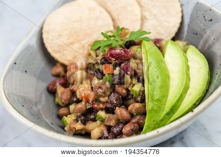 Legumes salad with crackers and avocado on marbel desk.