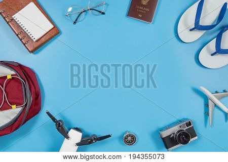 Travel gadgets and accessories on blue copy space in the middle