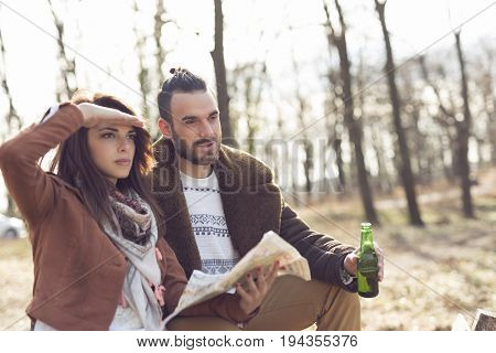 Young couple sitting on a wooden bench by the forest road reading the map and planning the route looking at the road ahead. Focus on the boyfriend