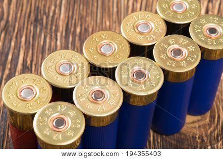 Large cartridges from the gun stand on a wooden table in a row