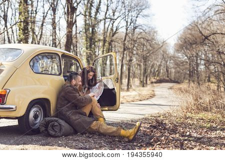 Young couple in love taking a break on their road trip sitting by the road and looking at a map trying to decide their route. Focus on the girl