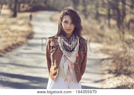 Portrait of a beautiful young brunette standing on the forest road in autumn