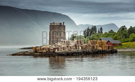 Tower of wooden pallets on the ocean. Scandinavian landscape. Norway