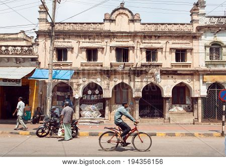 MYSORE, INDIA - FEB 20, 2017: Citylife with cyclist and motorcycle on street of indian city with buildings in colonial style on February 20, 2017. Mysore of Karnataka has a population of 900000