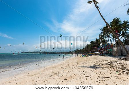 BORACAY, WESTERN VISAYAS, PHILIPPINES - JANUARY 11, 2015: Wide angle picture of kiteboarding and windsurfing at the beautiful beach of Bulabog.