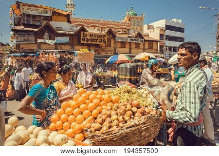 MYSORE, INDIA - FEB 16, 2017: Women buying fresh fruits and oranges on outdoor marketplace with many customers on busy asian street on February 16, 2017. Mysore of Karnataka has a population of 900000