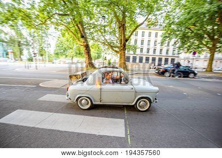 NANTES, FRANCE - May 27, 2017: Couple travel by retro car driving on the street in Nantes city in France