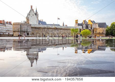 NANTES, FRANCE - May 27, 2017: View on the castle of Dukes of Brittany with water mirror fountain and tourists in Nantes city in France