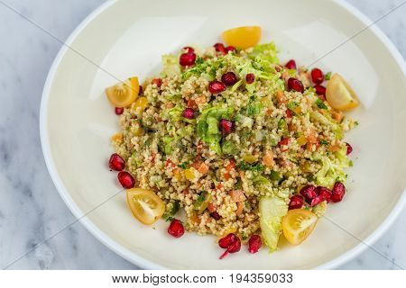 Quinoa salad with pomegranate in white plate on marbel decks
