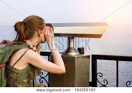 Woman looking in touristic spyglass at Mediterranian sea landscape