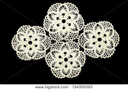 Lace doily on black background. White crocheted coaster on black background. Not isolated.