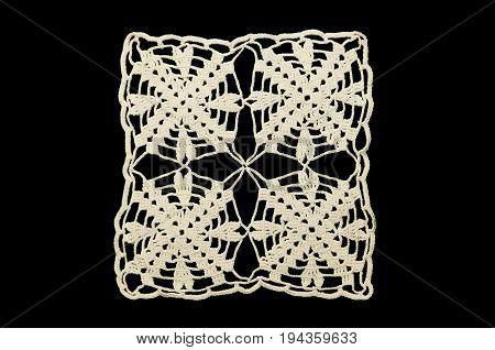 Lace doily on black background. White crocheted coaster on black background. Not isolated