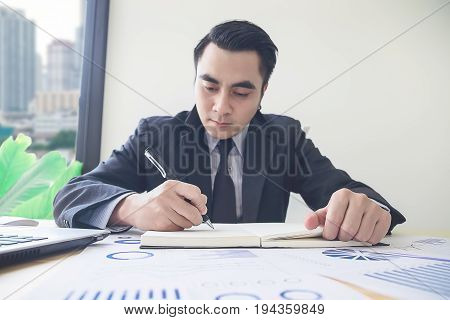Close-up Of Businessperson Signing Contract,man Writing Paper At The Desk With Pen And Reading Books