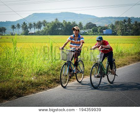 Mekong Delta Vietnam - Mar 23 2016. Boys biking on road in Mekong Delta Vietnam. The Mekong Delta is a rich lush area where the mighty Mekong River stretches out to the sea.