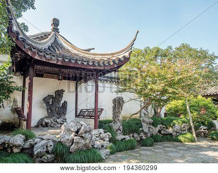 Suzhou, China - Nov 5, 2016: Master of Nets Garden (Wang Shi Yuan) - Pavilion housing naturally formed ornate boulder in a quiet garden area.