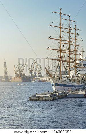 Large sailing ship in city port at berth, summer day