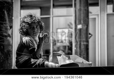 Hungry homeless beggar child on the street looking at the camera. Real beggar. With film grain. Black and white. Social documentary street. May - 20. 2017. Novi Sad, Serbia.