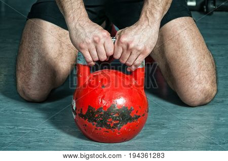 Man holding kettle bell with his hands on the gym floor. Kettle bell training workout.