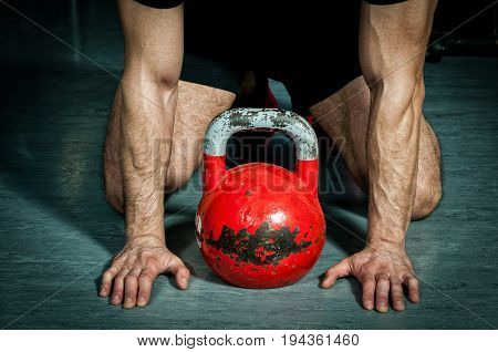 Man preparing for kettle bell training in the gym. Gym floor. Kettle bell workout.