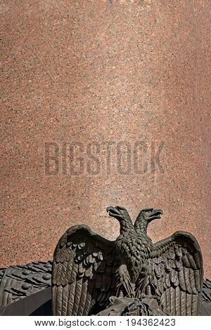 Two-headed eagle sculpture on a granite backdrop of the Alexander column on Palace Square in Saint Petersburg, Russia