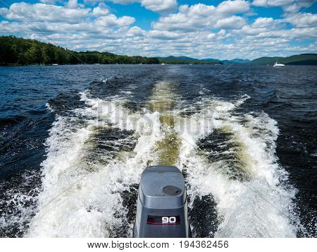 boat wake with outboard engine on a lake with boats in the background