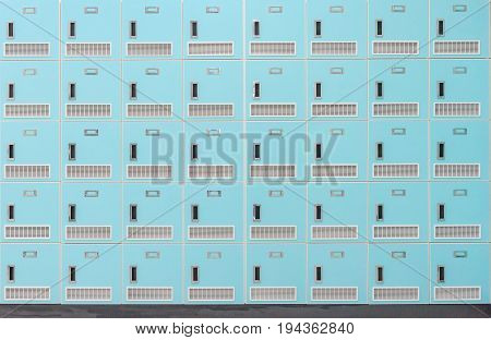 A front on view of a stack of Spring green metal school lockers with combination locks and doors shut as background