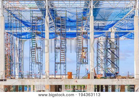 staircase and scaffolding on a construction site Structure of steel roof frame for building construction covered with mesh