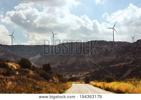 Wind turbines. Summer landscape with road, mountains and wind turbines.
