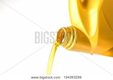 Pouring oil lubricant motor car from bottle isolated on white background Closed up