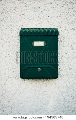 Green beautiful old fashioned mailbox on white wall background.
