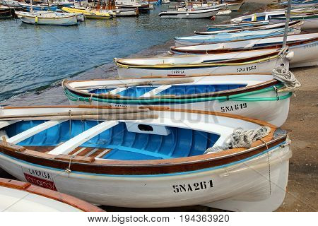 Small, colorful boats along the beach in Capri, Italy.