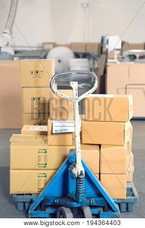 View of boxes stacked on trolley in distribution warehouse