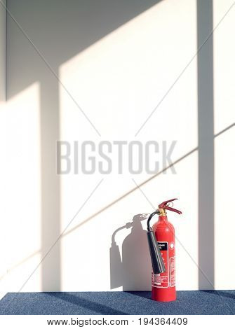 View of a fire extinguisher casting shadow on wall