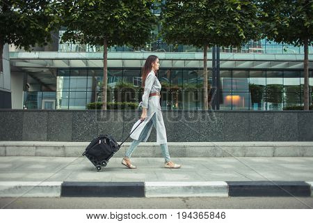 young woman with touristic bag walk on clean street of modern city at summer day