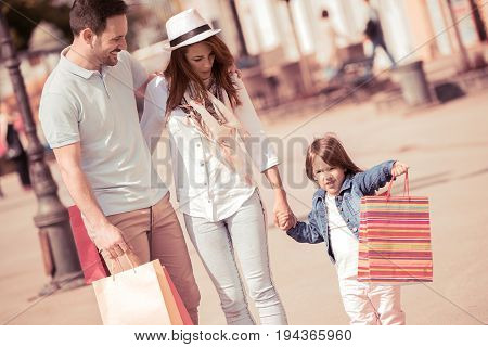 Parents walking with daughter on sunny day in the city with shoping bags.