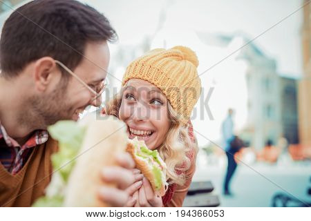 Young happy couple eating together outdoors and smiling.