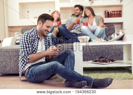 Handsome man surfing the net while spending time with friends.
