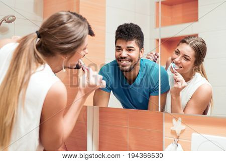 Woman brushing teeth in bathroom and looking in the mirror at reflection.
